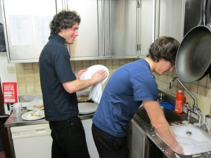 Sam Playfair (left) and Oli Johnes wash up after breakfast