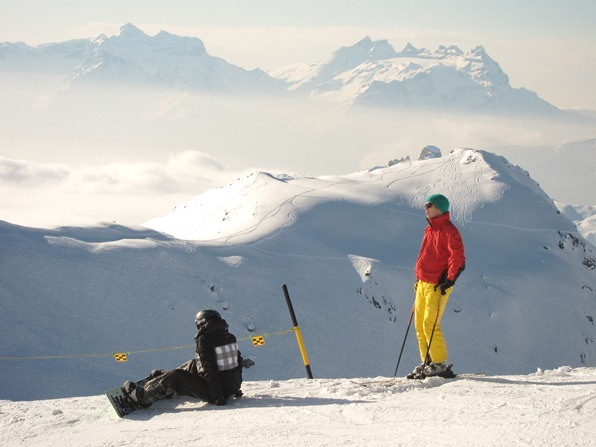 A skier and a snowboarder above Lac des Vaux, Verbier