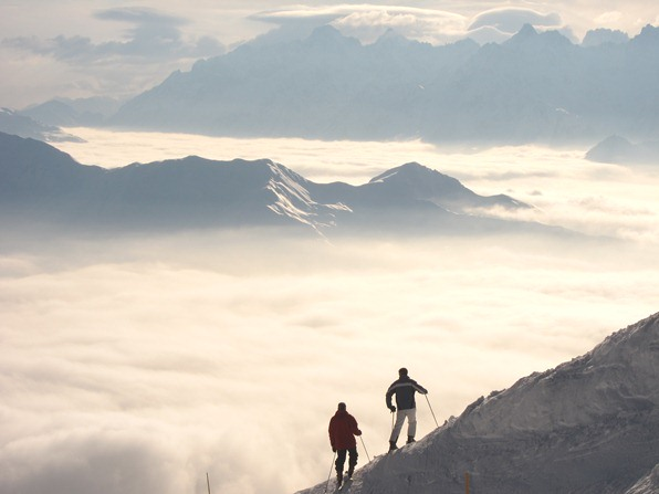 Two skiers looking out over the clouds, by the Attelas piste, Verbier