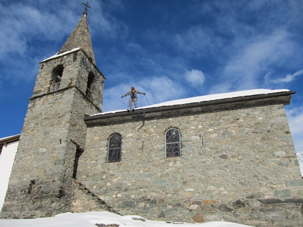 Statue of someone appearing to ski off the roof of the chapel in Verbier