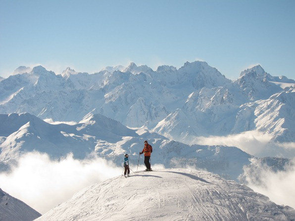 Two skiers near Chalet Carlsberg, Attelas piste, with Mont Blanc in the distance
